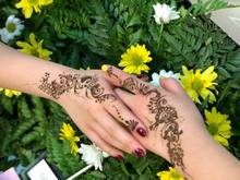 Photo of Mumtaz' work - decorated hands on a flower background